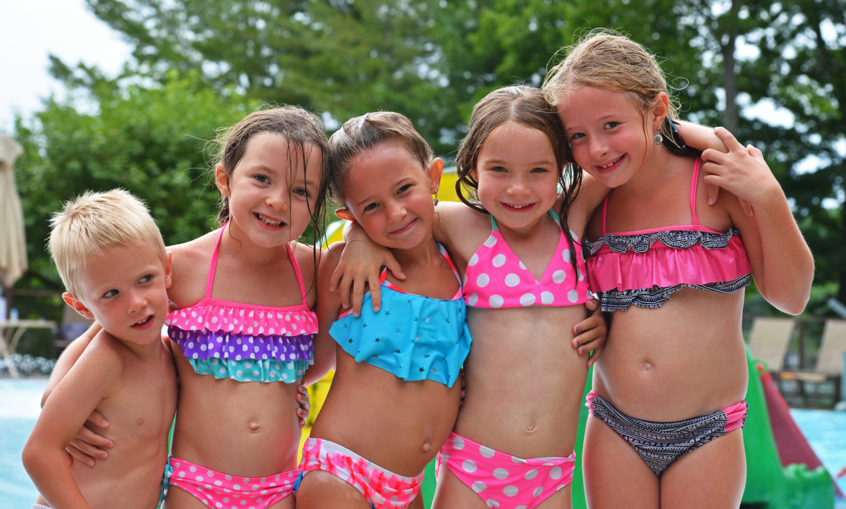 Young girls and boy posing by outdoor pool.
